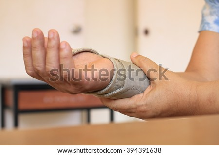 woman with wrist pain  in an Elastic Bandage - stock photo