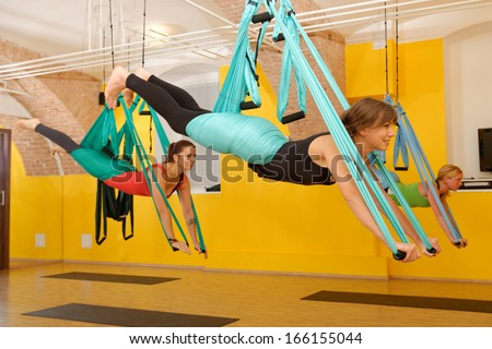 Women doing anti gravity Aerial yoga exercise in the gym - stock photo