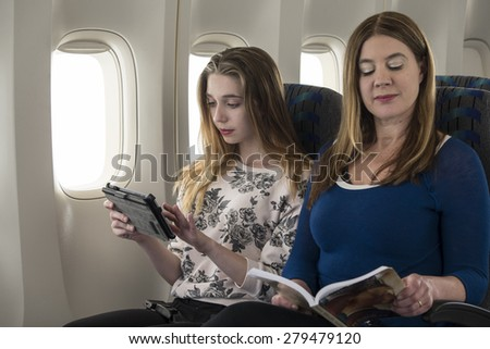 2 women reading and relaxed during their flight - stock photo