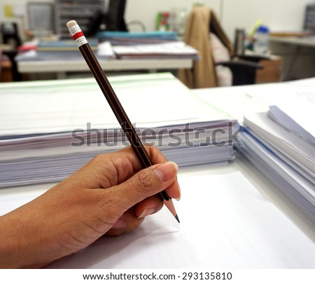 Women's hands grip a pencil writing on the white paper.                          - stock photo