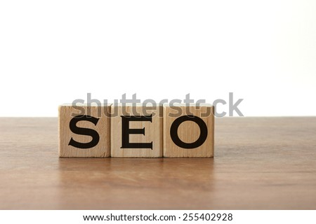 3 Wood Blocks With Letters Writing Out SEO, Front View, On Wooden Table, Light-Grey Background