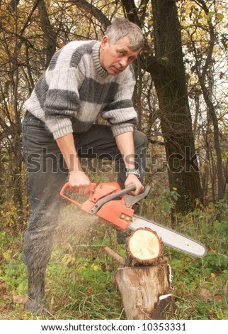 wood-cutter saw wood  red chainsaw - stock photo