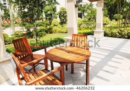Wood recreational chairs and table under pergola in a garden.