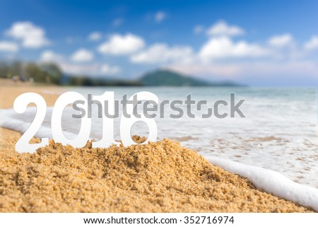 2016 wooden character on sand beach with wave and blue sky, New year concept