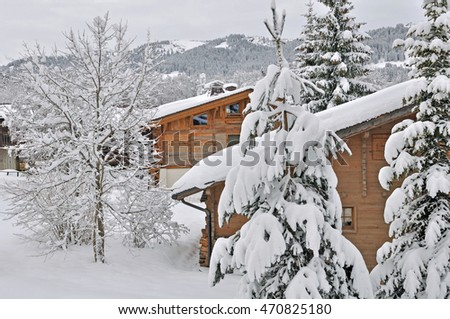 wooden cottages facade in the firs snowing on a mountain village