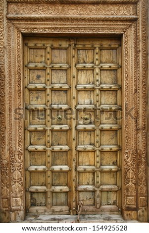 Wooden door with ancient floral patten. Wood carving technic - stock photo