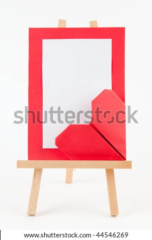 wooden easel with blank canvas and paper heart on white background