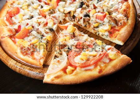 Wooden plate of fresh baked pizza . - stock photo