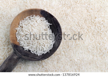 wooden spoon with thai rice on background of grains of rice - stock photo