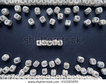 Word Bonus of small white cubes next to a bunch of other letters on the surface of the composition on a dark background