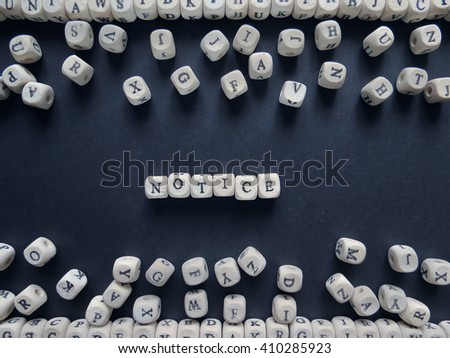 Word Notice of small white cubes next to a bunch of other letters on the surface of the composition on a dark background
