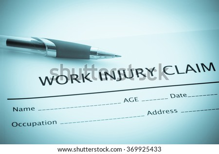 Work injury claim form showing business insurance concept with pen.
