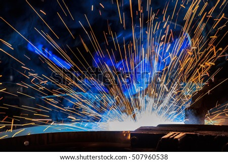 worker is welding metal with  sparks and torch