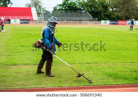 worker mowing the lawn at soccer stadium.