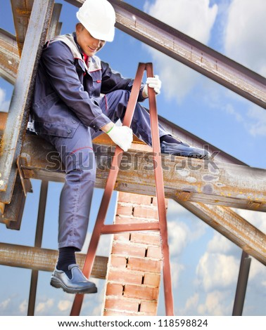 Worker On A Steel Beam Raises His Hands Sitting On The