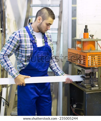 worker working on a machine in PVC shop - stock photo