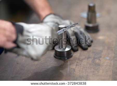 workers hand measuring a metal workpiece  - stock photo