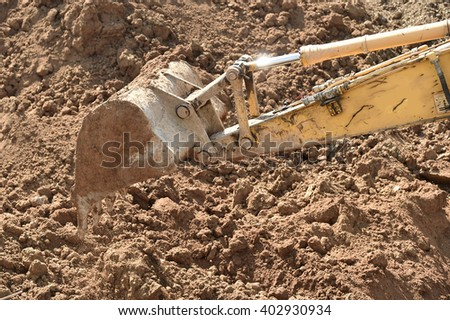 Working excavator that loads ground on construction site