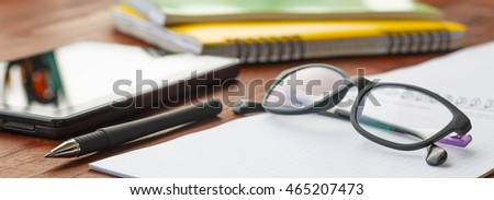 workplace of the student, a businessman. Notebook, laptop, tablet PC, glasses at office desk, on a school desk. Concept: the beginning of the working day, the beginning of the study, on 1 September.