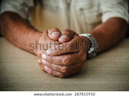 Wrinkled hands elderly man at table - stock photo