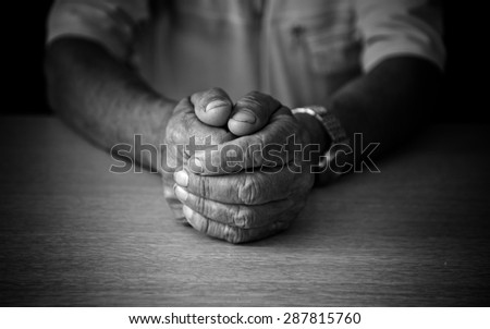 Wrinkled hands elderly man at table. Black and white photo - stock photo