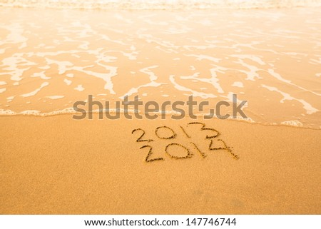 2013 - 2014 - written in sand on beach texture - soft wave of the sea. - stock photo