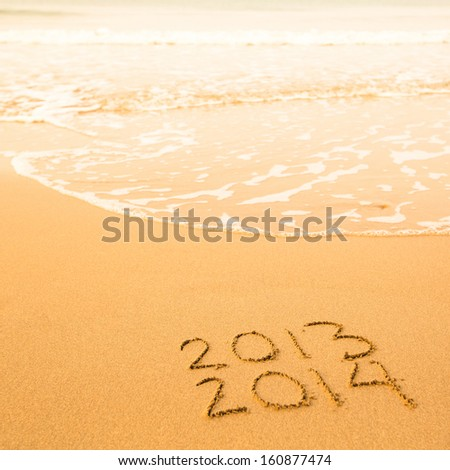 2013 - 2014, written in sand on beach texture, soft wave of the sea. - stock photo