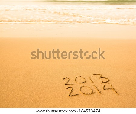 2013 - 2014 written in sand on beach texture, soft wave of the sea. - stock photo