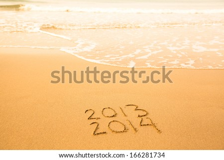 2013 - 2014, Written in sand on beach texture, soft wave of the sea - stock photo