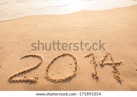 2014 written in sand on the beach