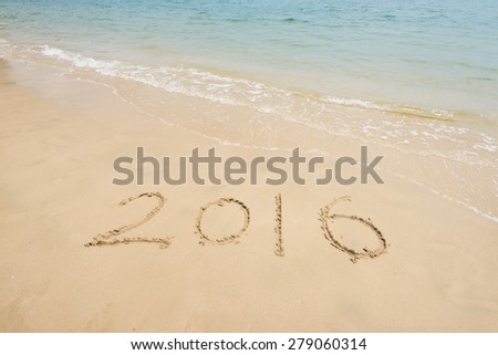 2016 written in sand, on tropical beach - stock photo