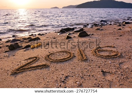 2016 written in sand on tropical beach, with sea in background - stock photo