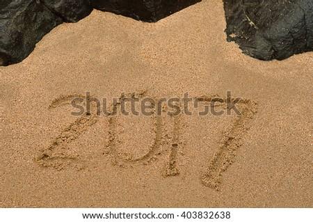 2017 written in sea sand on the beach - stock photo