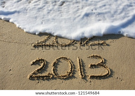 2013 written in the sand with 2012 washed away by the surf.