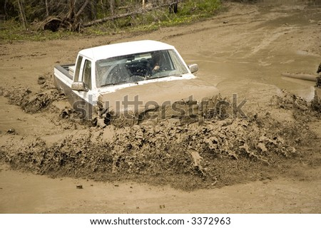 4x4 action through a huge mud hole. - stock photo