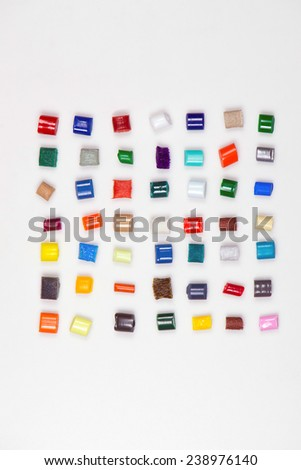 7 x 7 different polymer granulates in different colors on white in file - stock photo