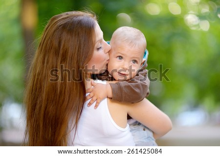 1 year baby in the arms of mother, blond, gray eyes, in a brown jacket, blue jeans, Mum beautiful brunette with straight hair, a white T-shirt. Green trees. Young mother with her baby in her arms. - stock photo
