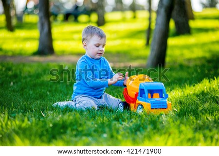 3 year baby sitting on the grass in the park plays a toy car on a background of green trees