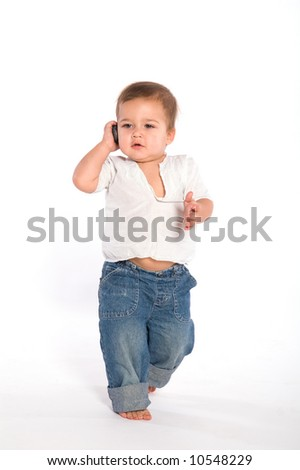 1 year baby walking and speaking by the phone - stock photo