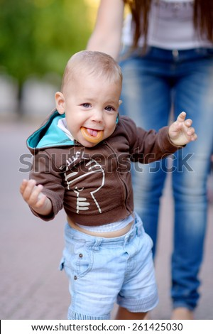 1 year baby with bagel, blonde, gray eyes, in a brown jacket with a hood, blue jeans. Against the background of green trees. - stock photo