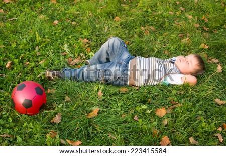 3-year boy laying on an autumn grass  - stock photo