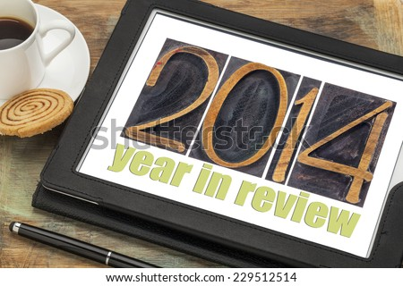 2014 year in review - text in letterpress wood type on a digital tablet with cup of coffee - stock photo