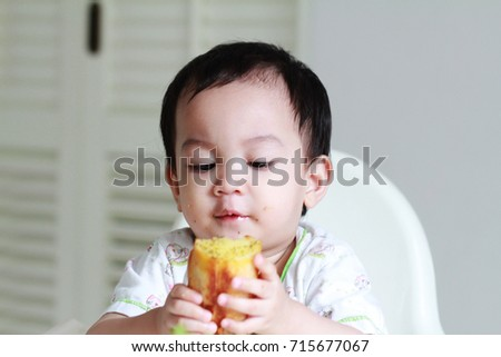 1 year old Asian boy enjoy his first sharp drop in his appetite.Boy eating cheese garlic bread smile and happy.Boy has increased activity,growth rate has slowed .So boy need more Nutrition  per day.