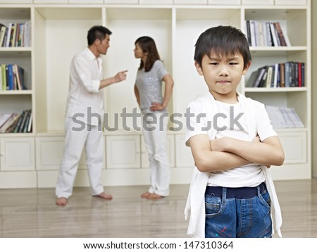6-year old asian boy with quarreling parents in background. - stock photo