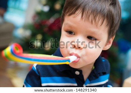 2 year old Asian Caucasian boy celebrates Christmas with a party blower and a Christmas tree in background - stock photo