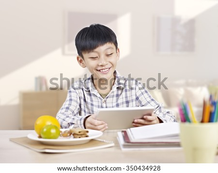 10 year-old asian elementary schoolboy looking at tablet computer and smiling. - stock photo
