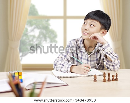 10 year-old asian elementary schoolboy looking away while studying at home. - stock photo