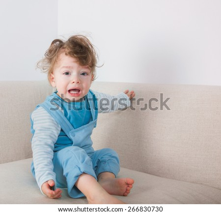 1 year old baby boy crying while sitting on the sofa. - stock photo