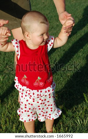 1 year old baby is practicing how to walk - stock photo