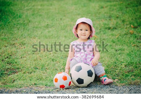 1 year old baby playing soccer football.